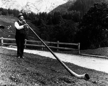 Alpine musician blowing his horn, c 1920s.