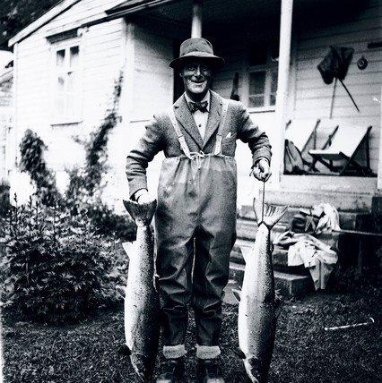 Angler holding up a pair of salmon, Eastern Seaboard, USA, c 1930s.