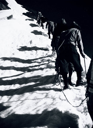 Mountaineers ascending a snow-covered peak, 1920s.