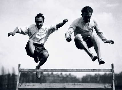 Two men jumping a steeplechase hurdle, c 1920s.