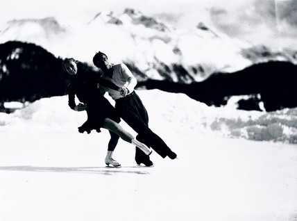 Couple skating on an ice rink in the mountains, c 1920s.