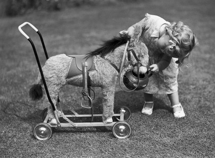 Small child playing with a toy donkey in a