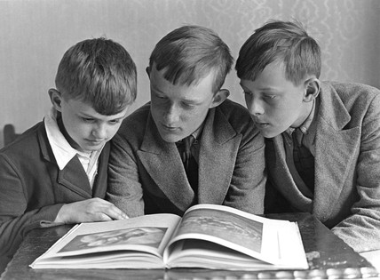 Three boys reading a book, c 1925-1935.