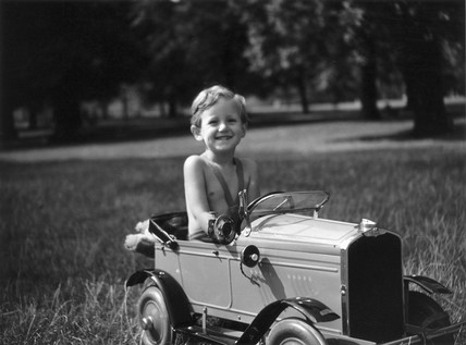 Little boy sitting in a toy car in the park