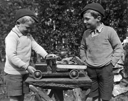 Two boys playing with a toy truck, c 1920s.