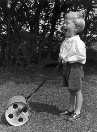 Small boy holding a lawn roller, c 1930s.