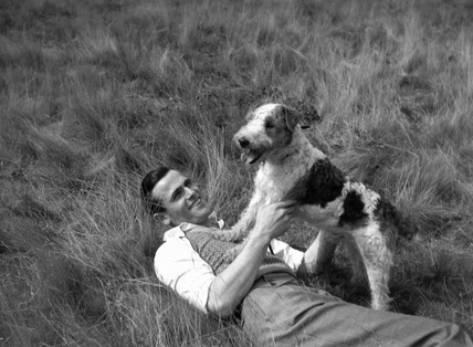 Man playing with a dog, c 1930s.
