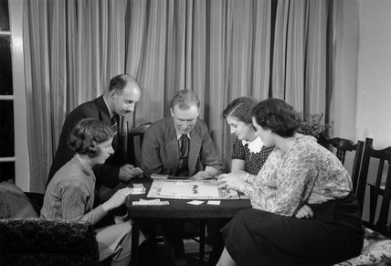 A family playing a game of Monopoly, c 1930.