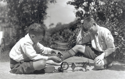 Two boys playing with a Meccano set, c 1930s.