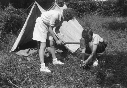 Young girl hammering a tent peg, asisted by her friend, c 1930s.