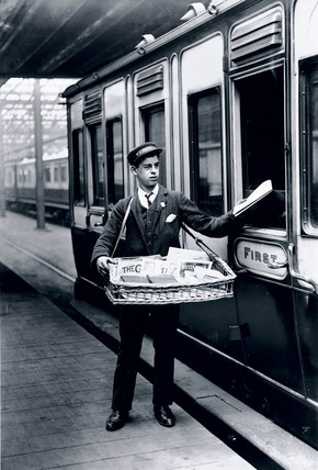 Boy selling newspapers, Holyhead Station, Wales, c 1905.