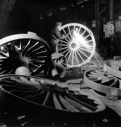 Burning the exces metal off the rough, unmachined, driving wheel, c 1958.