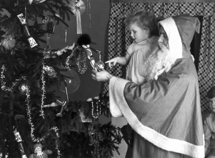 Father Christmas and a young child, c 1930.