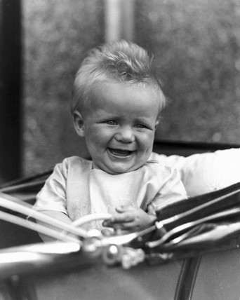 Baby sitting in a pram, c 1930s.