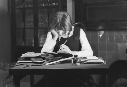 Schoolgirl doing her homework, c 1930s.