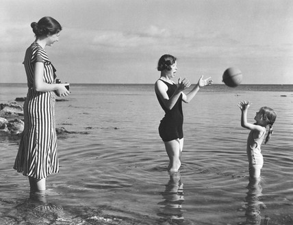 Woman taking  a photograph at the seaside, c 1930s.