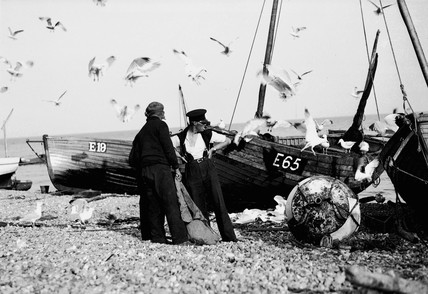 Three fishermen standing by their boats as seagulls hunt for scraps, c 1930s.