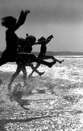 Silhouetted children jumping into the sea,