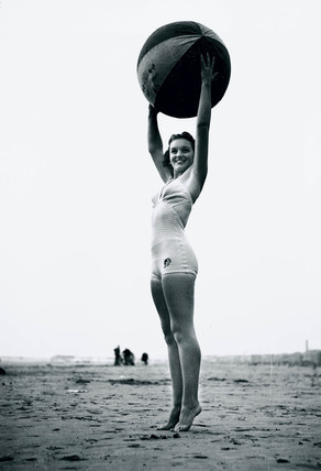 Young woman on tiptoes holding aloft a beach ball, c 1940s.