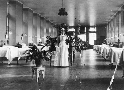 Nurse posing for camera in a hospital ward, c 1900s.