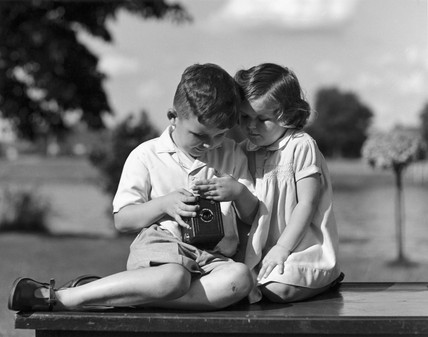 Two children inspecting a box camera, c 193