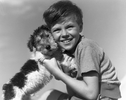 Young boy with a dog, c 1930s.