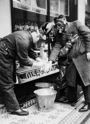 Decontaminating a man's hand using bleach, c 1940.