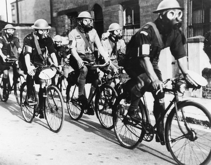 Rover Scouts wearing gas masks cycling in Portsmouth, 14 July 1937.