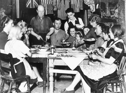 Families eating Sunday dinner, World War Two, 3 September 1944.