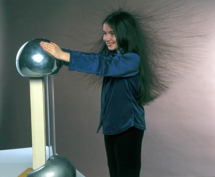 Girl holding a Van de Graaff generator, 1998.