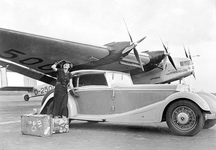 Woman standing alongside a Mercedes-Benz motor car, 1935.