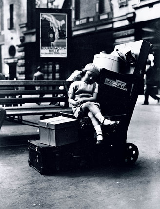 A girl asleep on a porter's trolley, Victoria Station, London, 3 July 1931.