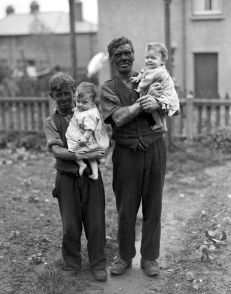 A miner and his family, Rhondda Valley, South Wales, 22nd June 1931.