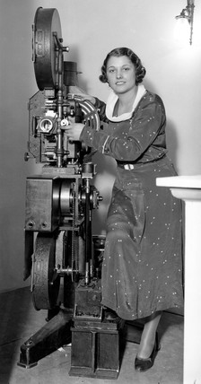 Woman model demonstrating cine projector at exhibition, 30 May 1932.
