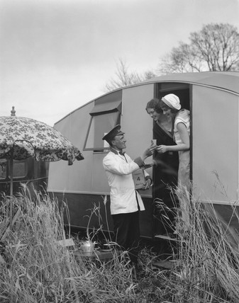 Women buying ice creams from vendor outside their caravan, 11 April 1931.