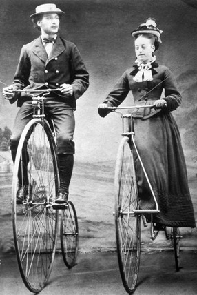 Lady and gentleman riding 'ordinary' bicycles with Starley wheels, 1874.