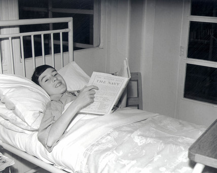 Boy in hospital bed reads book on the Navy, 23 December 1938.