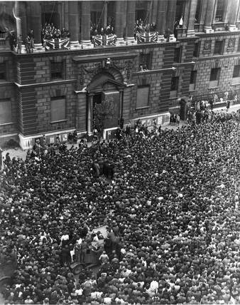 Winston Churchill speaking from a balcony.
