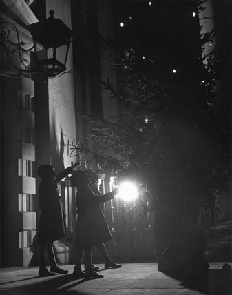 Children gather at night around a Christmas tree, 16 December 1935.