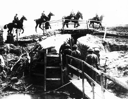 Australian Mounted Cavalry crosing a wooden bridge over a trench.