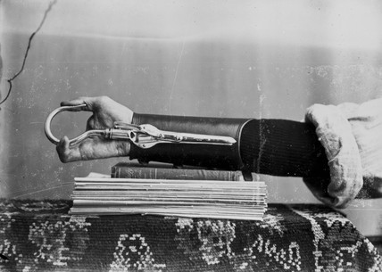 Man wearing a prosthetic device for the arms and hand, 1890-1910.