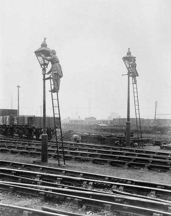 Women railway workers obscuring gas lamps, Greater Manchester, May 1917.