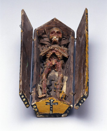 Stylised model of a decomposing corpse in a coffin.