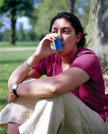 Young woman using an asthma inhaler, May 2000.