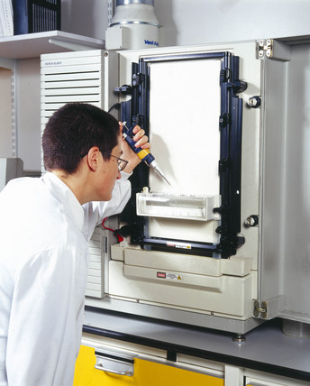 Molecular geneticist loading samples onto an automated DNA sequencer.