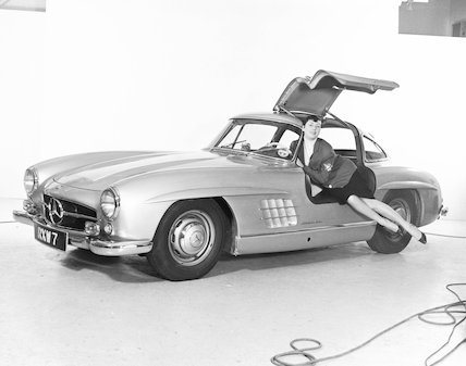 Model reclining in Mercedes wing-door car, c 1961.