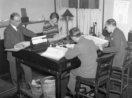 Four clerks at work in an office, October 1