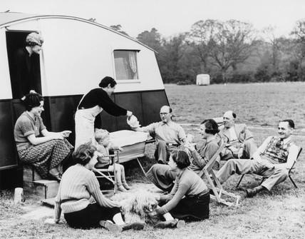 Camping Club member realxing outside caravan, c 1950s.