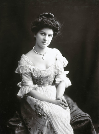Young woman sitting in an elaborate dres,  1890s.