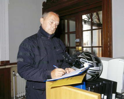 Motorcycle courier collecting a package for picture library clients, July 2001.